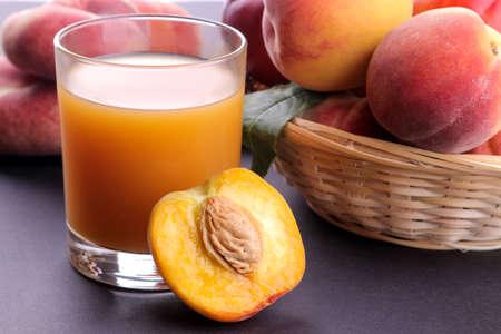Peach juice in a glass next to a fresh peach closeup on a dark background