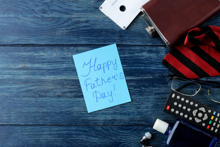 Happy father's day. Text on paper and man's tie, glasses and men's accessories on a blue wooden table. men's holiday. top view
