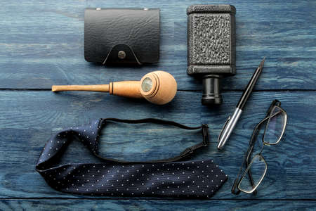 Men's Accessories.men's style. Glasses, business card holder, cigar, smartphone, notebook, headphones, and a pistol-lighter on a blue wooden background. Lay lay. Stock Photo