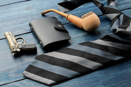 Various male accessories on a blue wooden table. tie and smoking pipe. Stock fotó