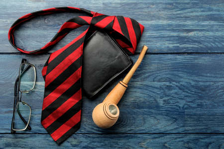 Various male accessories on a blue wooden table. tie and smoking pipe. top view