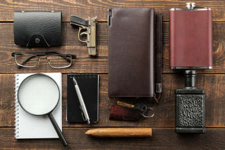 Men's Accessories. men's style. purse, flask, smoking pipe, perfume, business card holder, notebook, keys, glasses, cigar, on a brown wooden background. flat lay. Stock Photo