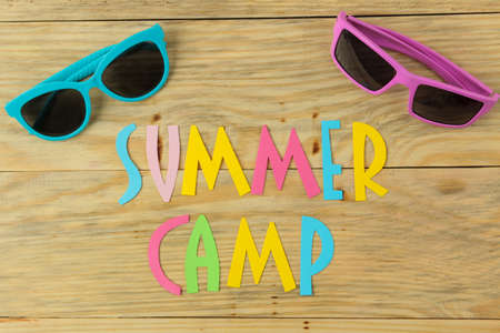 Text SUMMER CAMP of multicolored paper letters and sunglasses on a natural wooden background. top view. flat lay