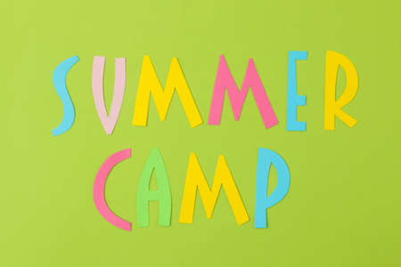 Text SUMMER CAMP of multicolored paper letters on a bright green background. top view. flat lay