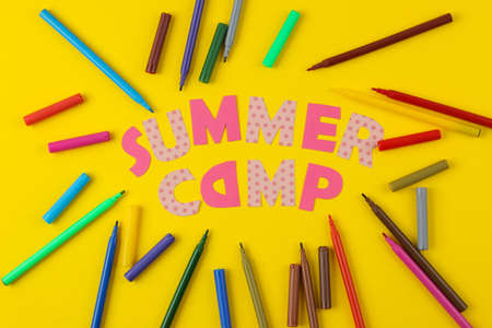 Text SUMMER CAMP of multicolored paper letters and colored felt-tip pens on a bright yellow background. top view. flat lay