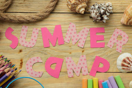 Text SUMMER CAMP of multicolored paper letters and rope and colored chalk on a natural wooden background. top view. flat lay