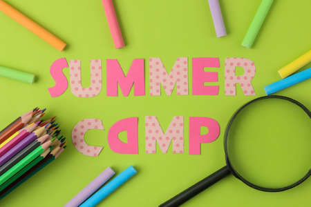 Text SUMMER CAMP of multicolored paper letters and crayons, pencils on a bright green background. top view. flat lay