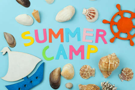 Text SUMMER CAMP from multicolored paper letters and sea scenery against a bright blue background. top view. flat lay