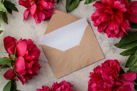 Beautiful bright pink flowers peonies and an envelope with a blank and on a bright concrete background. top view. space for text Zdjęcie Seryjne
