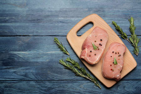 Raw pork steak on the board, meat and ingredients for cooking, spices herbs and vegetables on a light background. top view