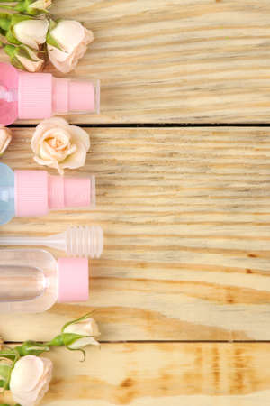 Face and body cosmetics in pink bottles with fresh roses on a natural wooden background. creams and lotion. spa. top view. space for your text