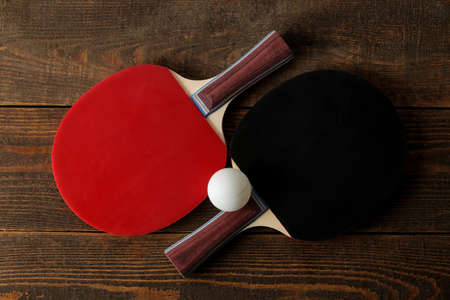 Two table tennis rackets. Table tennis rackets and a ball on a brown wooden table. sport game. top view Foto de archivo
