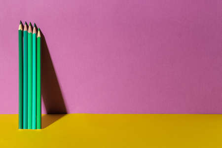 Several green pencil with a shadow on a trendy purple and yellow background. Space for text