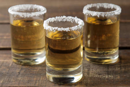 Gold tequila in a glass with salt and lime on a brown wooden table. alcoholic beverages.
