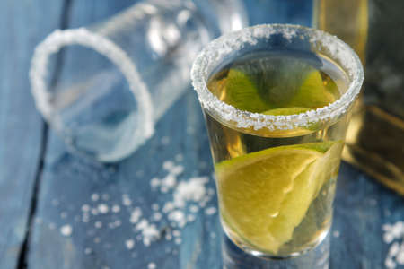 Gold tequila in a glass with salt and lime on a blue wooden table. alcoholic beverages. close-up