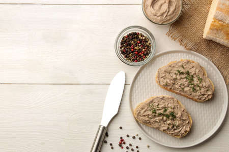 Fresh homemade chicken liver pate with herbs for bread on a white wooden table. A sandwich. top view