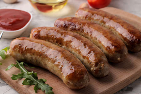 Delicious grilled sausages on a board with red sauce and spices on a light background. BBQ