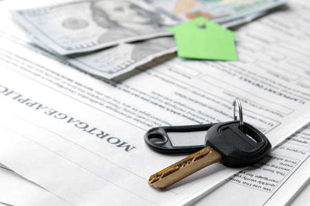 mortgage application. Key with house key fob and blank and money on a brown wooden table. concept of buying a home.