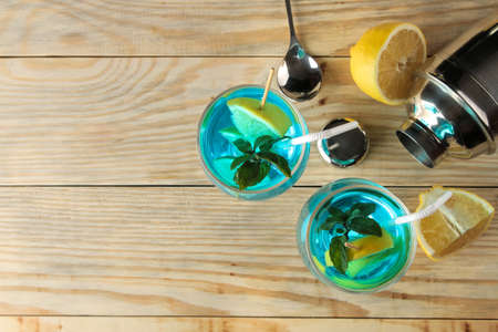 Cocktail in a cocktail glass with lemon and mint on a natural wooden table in the bar. cool summer cocktail Фото со стока