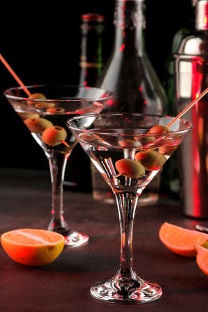 Martini. Alcoholic drink martini with olives in a glass on a dark background in the bar on the bar counter. bar inventory. cocktails