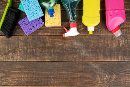 Different bottles with cleaning products and detergents and washcloths in a blue bucket on a brown wooden table. top view
