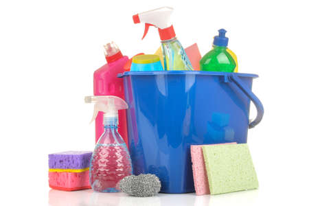 Various bottles with cleaning products and detergents in a blue bucket on a white isolated background.