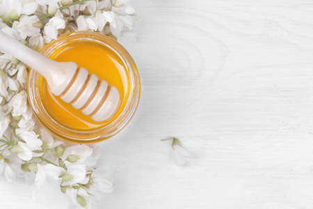 A jar of honey with a wooden spoon for honey and an acacia branch on a white wooden background. top view