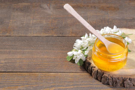 A jar of honey with a wooden spoon for honey and an acacia branch on a wooden pedestal. Brown background