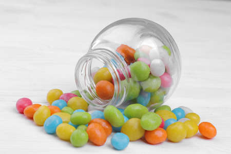 Multicolored round candy in a glass jar on a white wooden background.