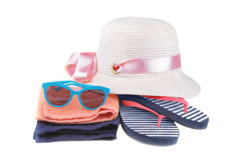 Summer hat with flip flops in a blue and white strip next to an orange and blue towel and blue glasses. Isolated