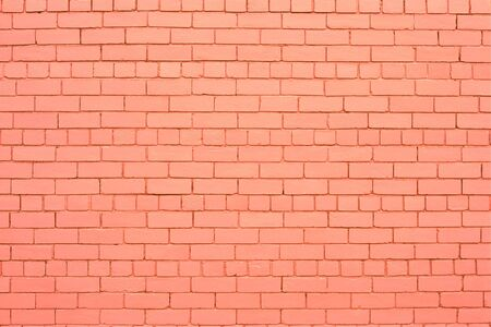 Soft pastel pink (salmon color) painted brick wall.