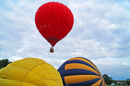 Balloons of red, blue, yellow, light green and orange inflate before climbing into the sky on a green glade