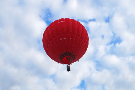 Red balloon rises into the sky with white clouds on a summer day