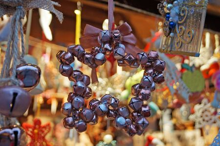 Christmas tree decorations made of glass, wood and fabric of different shapes and colors on the counter at the festive fair