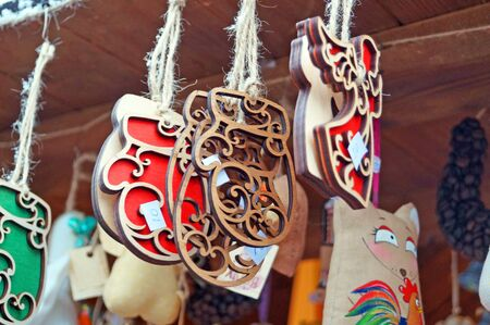 Wooden Christmas tree decorations hanging on a counter at a festive fair