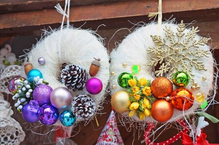Christmas wreath of fir branches decorated with colorful Christmas balls on a winter day at the festive fair