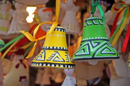Christmas tree decorations made of ceramic in the form of bells and angels at the festive fair