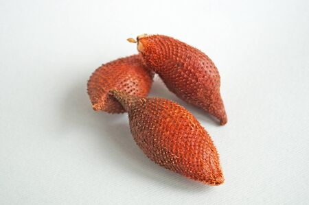 Exotic herring fruit with brown scaly skin and juicy white pulp on a light background
