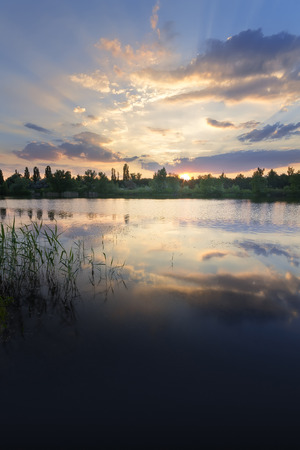 the sunset on the lake on a summers evening  bright summer photo of the suns rays Ukraine