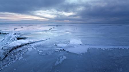 湖の冬の寒い朝、夜明けと太陽の光を待っている 写真素材