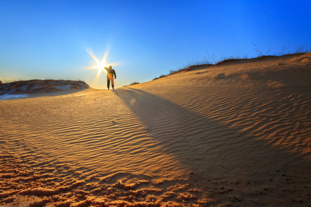 walking through the dunes  man holding the sun in his hand