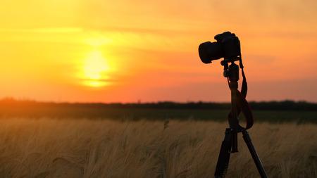 camera tripod sunset  decided to take your camera on the sunset background Reklamní fotografie