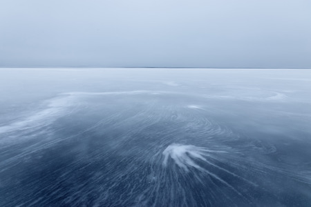 fancy patterns on the ice / early morning fog haze on the horizon Stock Photo