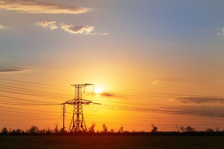 sunset on the background of power lines / bright colors of spring landscape