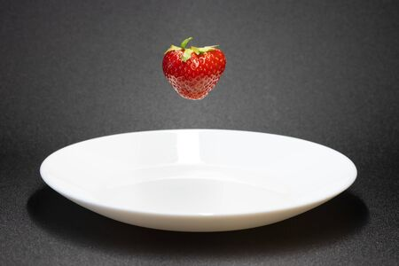 strawberry close-up .floating strawberry over a plate 版權商用圖片