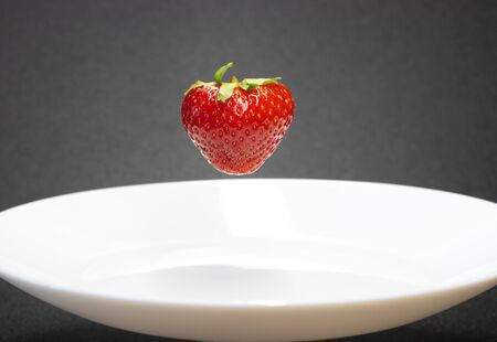 strawberry close-up /floating strawberry over a plate