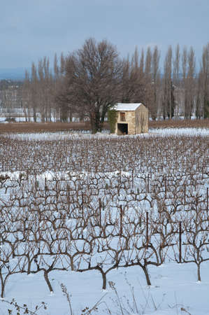 enclave: cabin in stone under snow in the middle of the fields Stock Photo