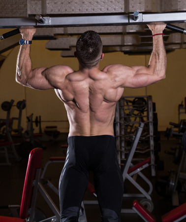 Muscular Young Man Doing Pull Ups  Chin-Ups  in the Gym  photo