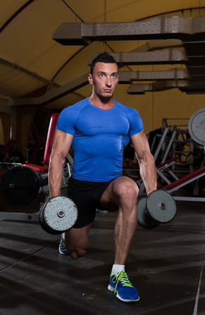 lunges: Muscular Men performing dumbbell lunges, one of the best leg exercise.