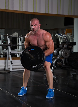 t bar: Muscular men exercising with weights. He is performing T bar rows for back muscle Stock Photo